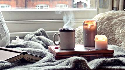 Coffee mug with candles and a view from a window