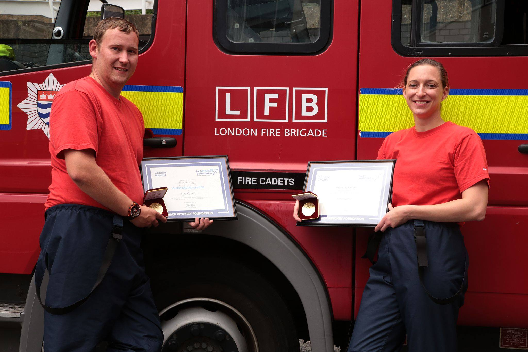 Firefighters standing in front of fire engine with their  awards