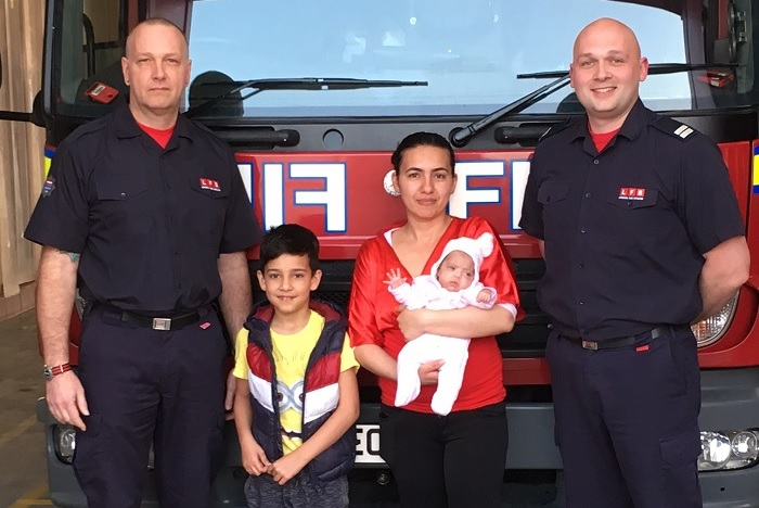 Tottenham Firefighters pose with a mother and her two children in front of a fire engine