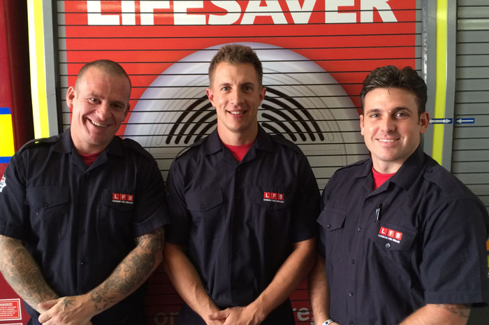Three of the Firefighters that helped deliver the baby stood in front of a fire engine