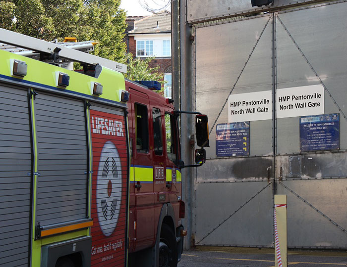 Side view of a fire engine as it pulls up the gates of Pentonville prison
