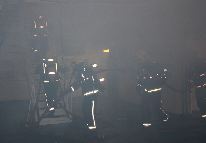 six firefighters can hardly be seen as they carry a hose through smoke and up a flight of stairs