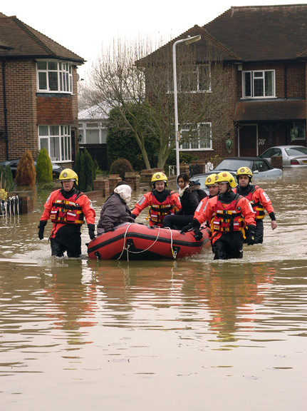 Firefighters rescuing a woman during flooding