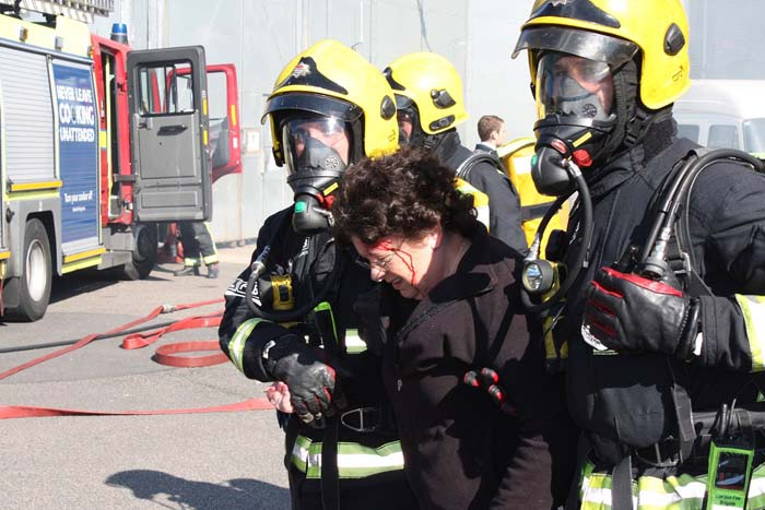 two firefighters are holding a woman up as she bleeds from the head in organised training exercise
