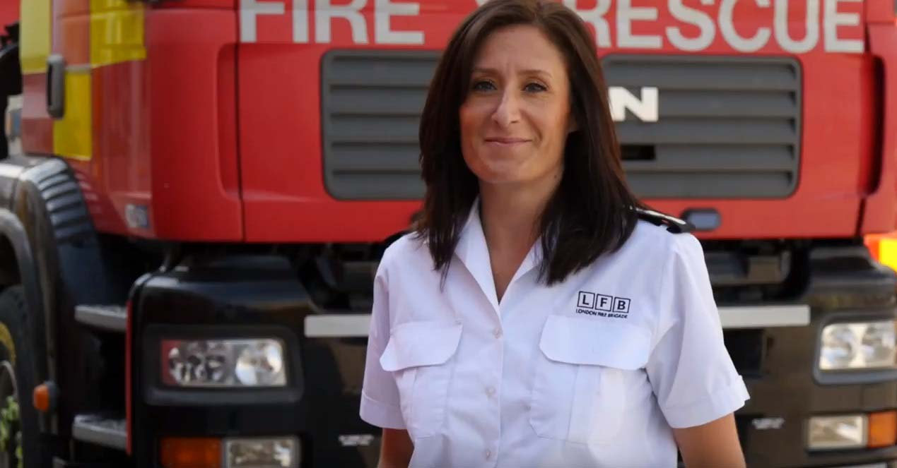 Station Manager, Victoria Metz smiling stood in front of a fire engine