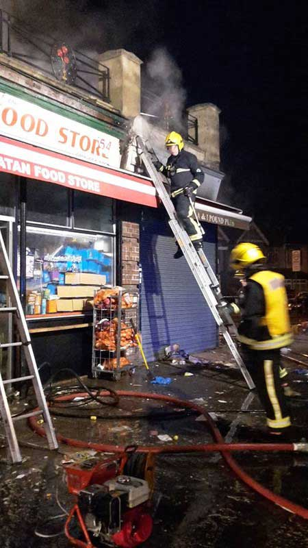 Two firefighters at a shop that is on fire, one is climbing a small ladder while the other looks at debris on the floor
