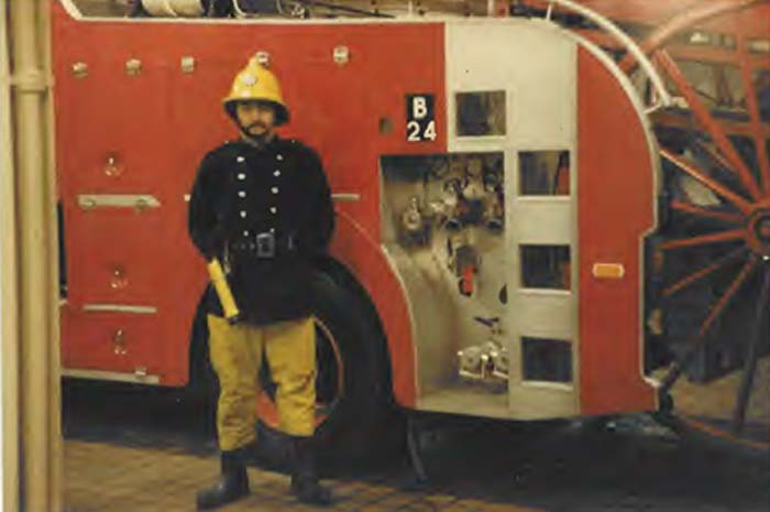 Steve Brooker in front of a Fire Engine wearing his uniform