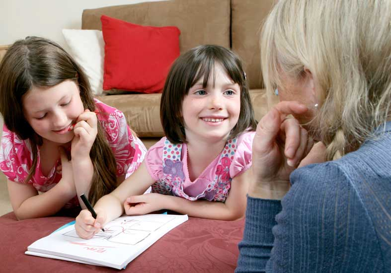 Two young girls drawing while  smiling at a family member