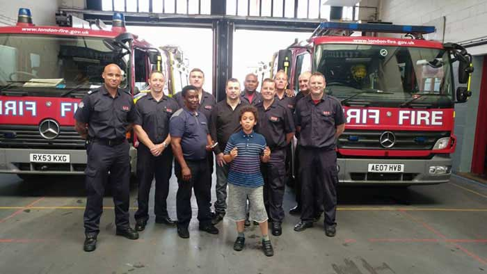 Group of firefighters stood in front of two fire engines with a man they rescued and his carer