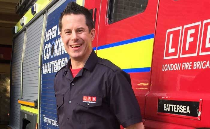 Stuart McDonald stood in front of a fire engine smiling