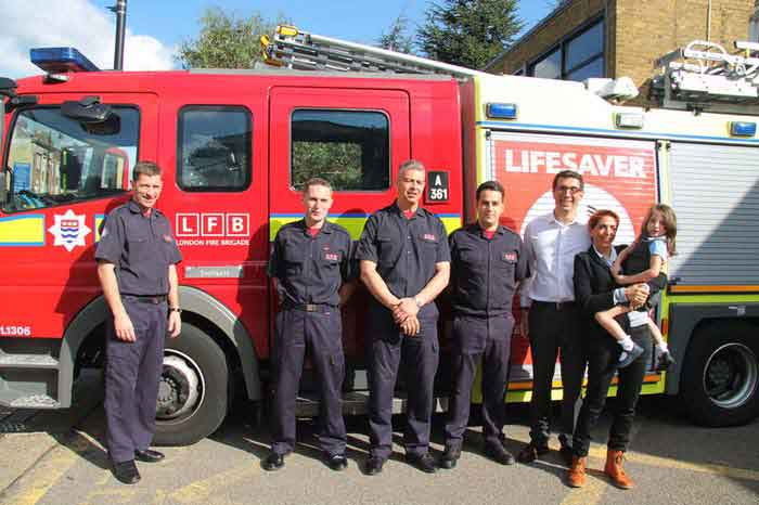 Poppy and her mum with four firefighters in the sunshine next to a fire engine