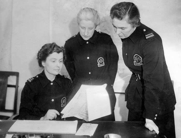 Black and white photograph of three female firefighters in uniform looking at a number of sheets of paper