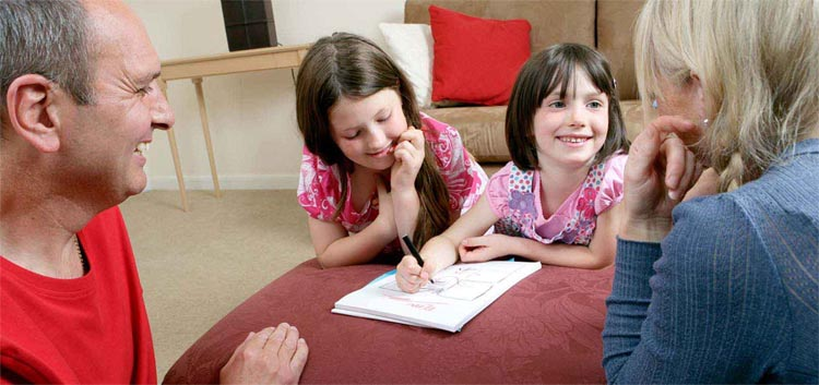 Two young girls drawing while smiling at family members