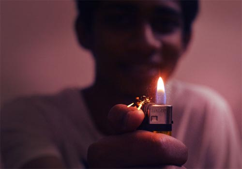 Young person with ignited lighter