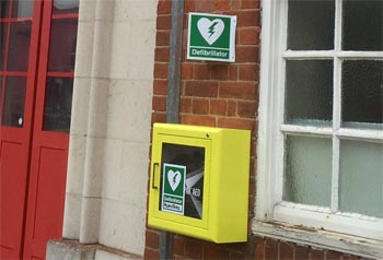 Yellow Defibrillator box on the wall outside Plumstead fire station