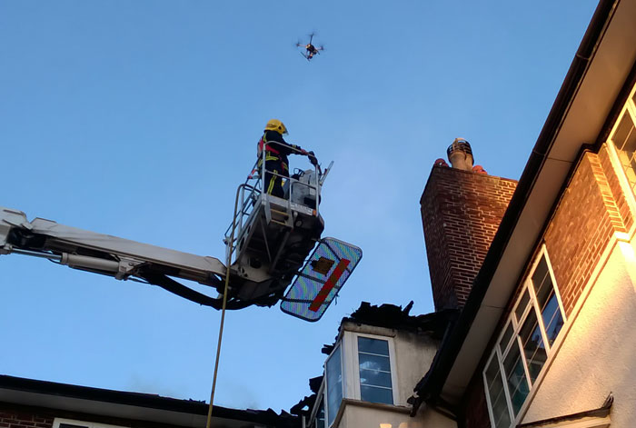 Drone hovering over firefighter working at height at an incident.