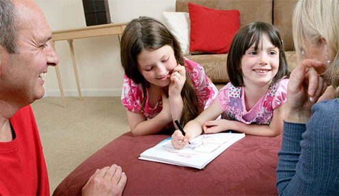 Parents helping children with activity sheets