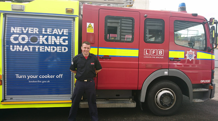 Firefighter Ian Tobin standing in front of a fire engine