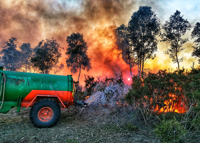 A tractor sprays water on to a grass fire on Thursley Common