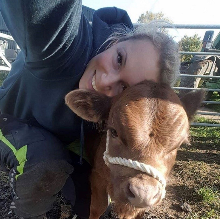 Firefighter Emily Butler pictures with a calf on her family farm